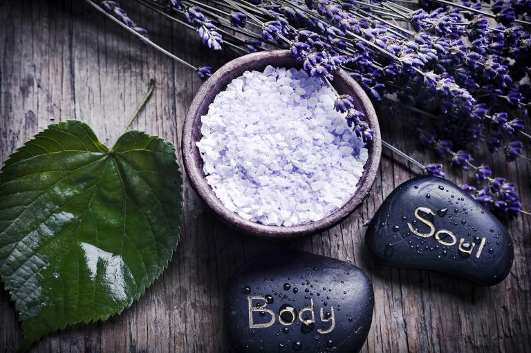A green leaf with healing stones, a bowl with lavender herb salt and dry French lavender.